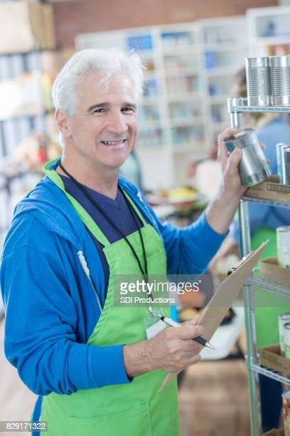 Confident man stocks shelves in food bank