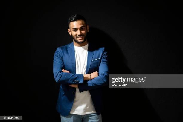 confident man with arms crossed standing against black background - dreiviertelansicht stock-fotos und bilder