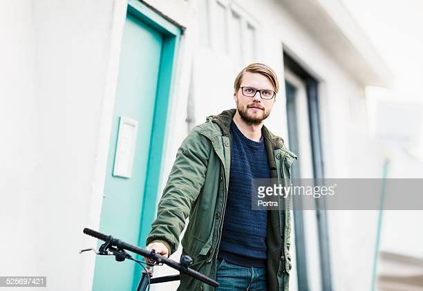 confident man with bicycle by building - parka coat stock photos and pictures