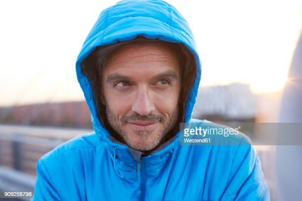 confident man with hooded jacket in the city - blue jacket stock pictures, royalty-free photos & images
