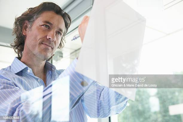 Confident man writing, leaning on window