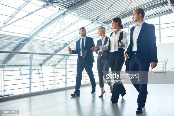 confident management team talking while walking - visita imagens e fotografias de stock