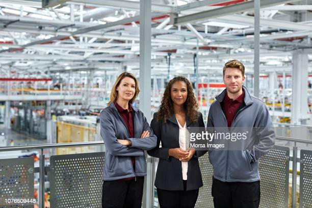 confident manager and engineers in car plant - railings stock photos and pictures