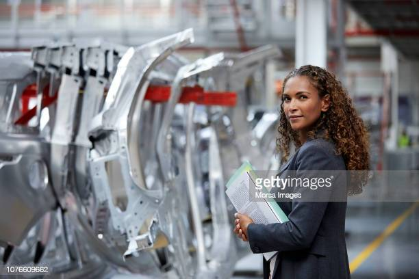 confident manager standing by chassis in car plant - stem stock pictures, royalty-free photos & images