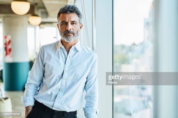 confident mature businessman at coworking space - businessman stock pictures, royalty-free photos & images