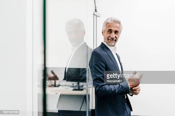 confident mature businessman in office - lehnend stock-fotos und bilder