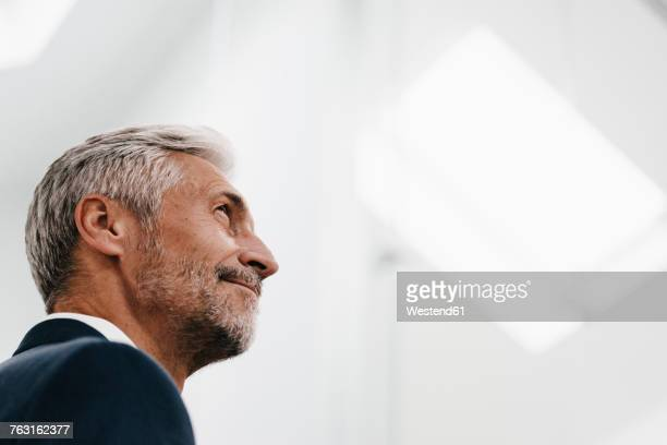 Confident mature businessman looking up