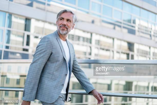 confident mature businessman on the go looking around - メンズウェア ストックフォトと画像