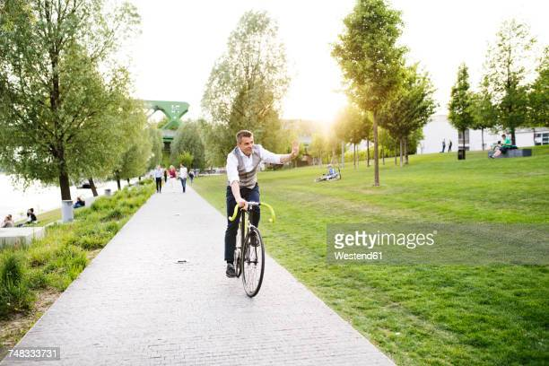 Confident mature businessman riding bicycle on waterfront promenade