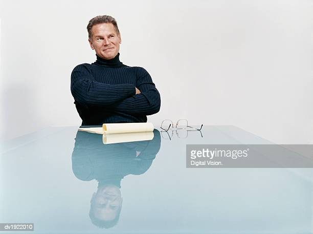 confident mature businessman sitting behind a glass table with his arms crossed - dolcevita foto e immagini stock