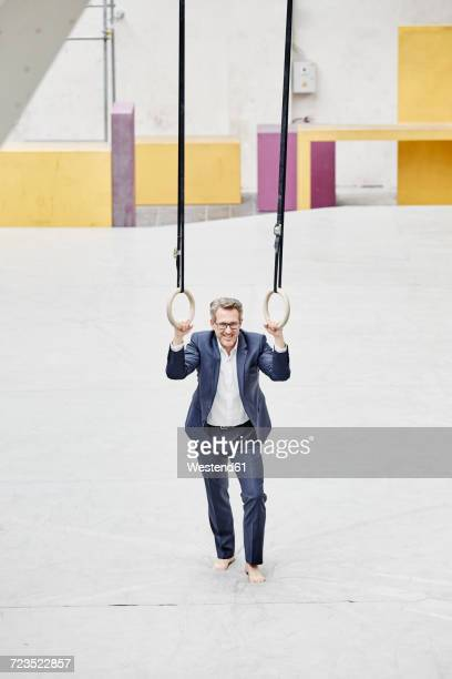 Confident mature businessman standing at gymnastic rings