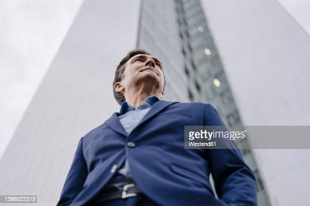 confident mature businessman standing in front of an office tower in the city - low angle view - fotografias e filmes do acervo