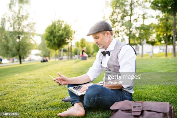 Confident mature businessman with laptop in the city park sitting on grass