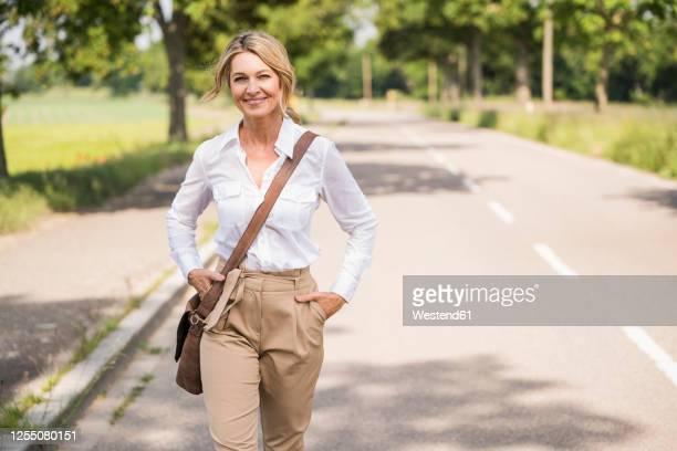 confident mature businesswoman carrying shoulder bag while walking on road - broek stockfoto's en -beelden