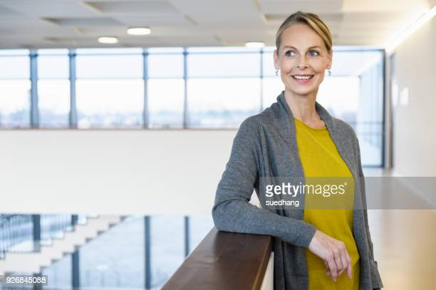 confident mature businesswoman in office atrium - cardigan sweater stock pictures, royalty-free photos & images