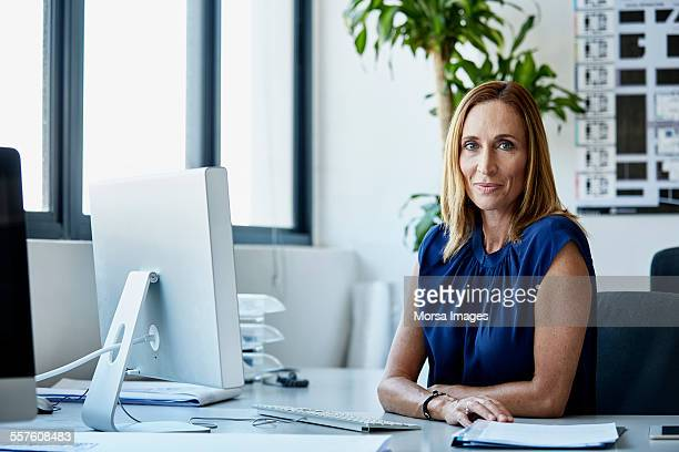 Confident mature businesswoman sitting at desk
