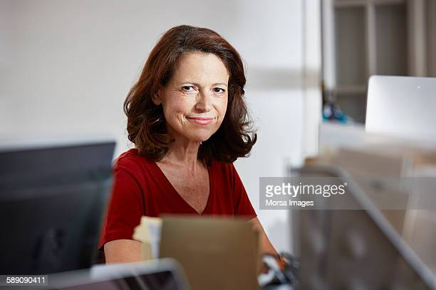 confident mature businesswoman sitting in office - mid length hair stock pictures, royalty-free photos & images