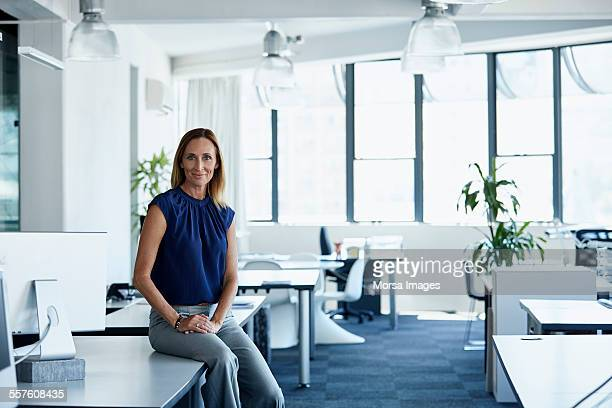 confident mature businesswoman sitting on desk - vestido azul fotografías e imágenes de stock