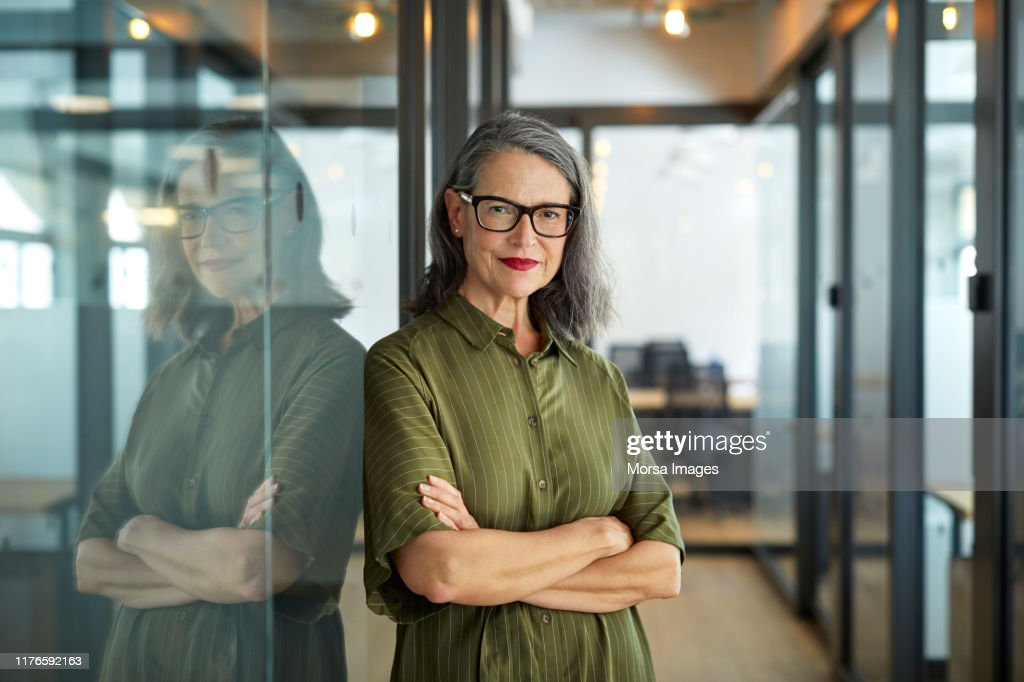 Confident mature businesswoman with arms crossed : Photo