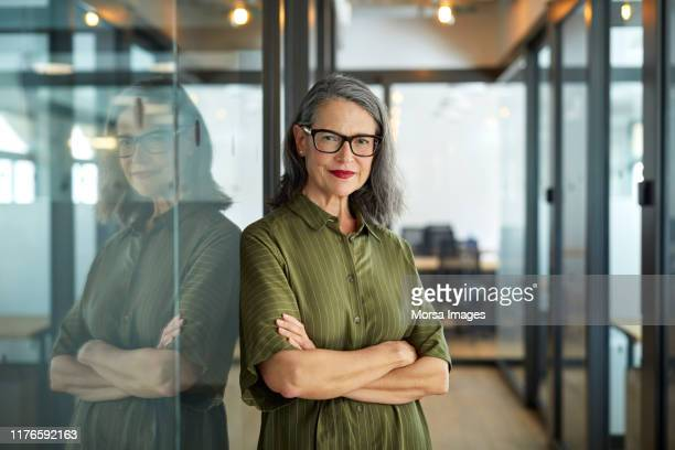 confident mature businesswoman with arms crossed - confidence stock pictures, royalty-free photos & images