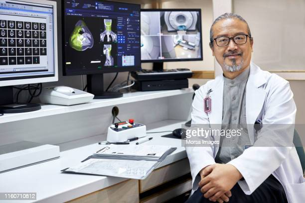 Confident mature doctor sitting by desk in office