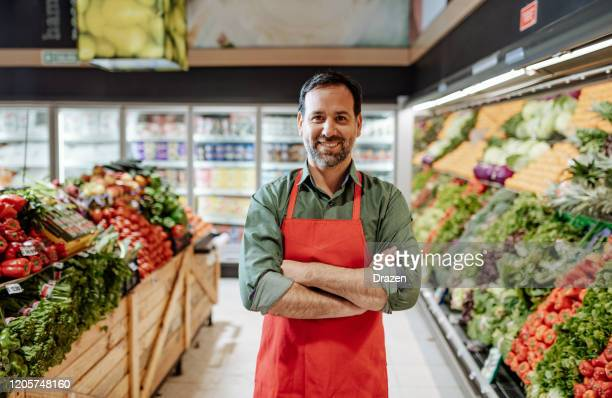 confident mature employee in supermarket, wearing red apron - salesman stock pictures, royalty-free photos & images