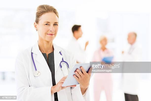 Confident Mature Female Doctor Using Digital Tablet In Hospital