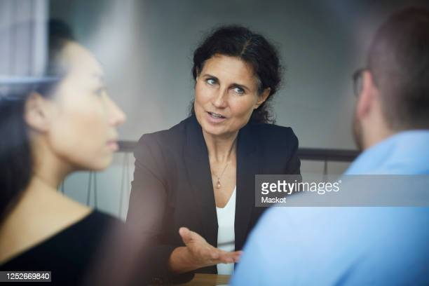 confident mature female financial advisor discussing with businessman and businesswoman during meeting at office - legal system stock pictures, royalty-free photos & images