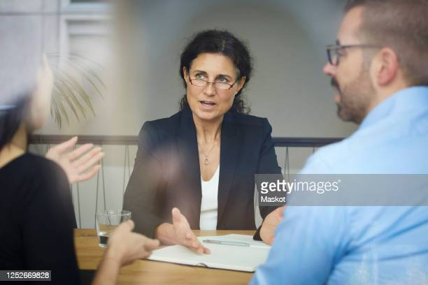 confident mature female lawyer discussing with businessman and businesswoman during meeting at office - lawyer stock pictures, royalty-free photos & images