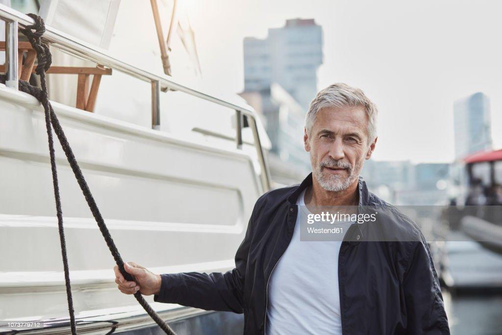 Confident mature man at a marina next to a yacht : Stock-Foto