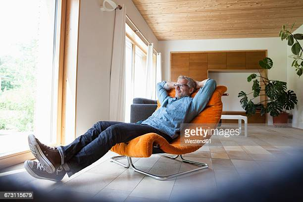 Confident mature man relaxing in armchair