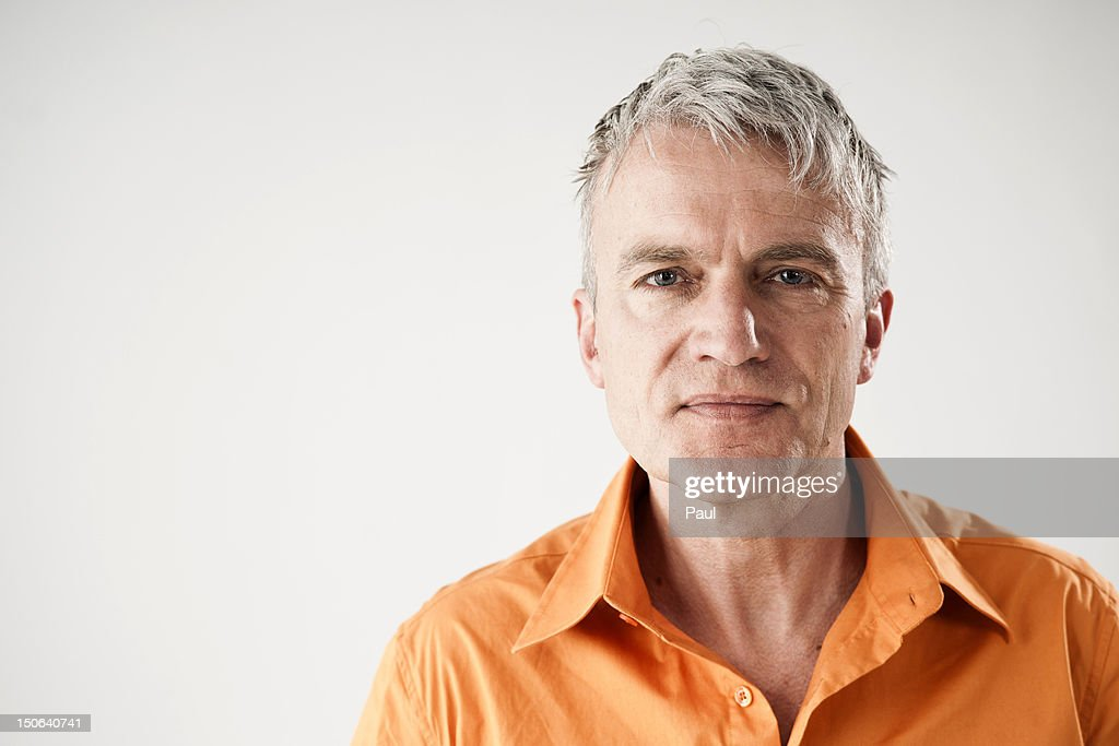 Confident mature man wearing orange shirt : ストックフォト
