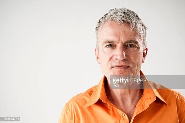 confident mature man wearing orange shirt - オレンジ色のシャツ ストックフォトと画像