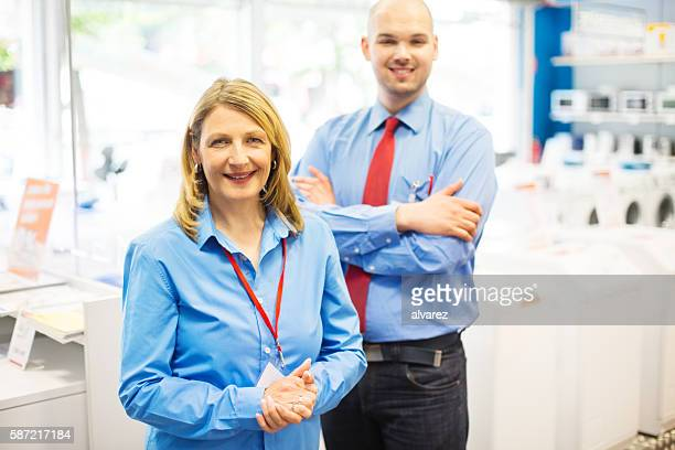 confident mature saleswoman at a retail store - electronics store stock photos and pictures
