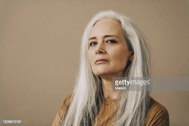 confident mature woman with white hair against beige background - white hair stock pictures, royalty-free photos & images