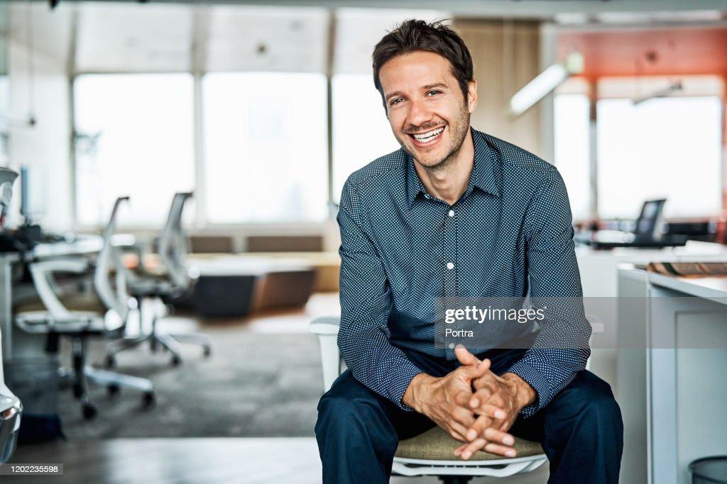 Zekere medio volwassen zakenman in bureau : Stockfoto