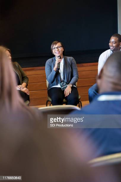 confident mid adult businesswoman speaking to crowd during conference - panel discussion stock pictures, royalty-free photos & images
