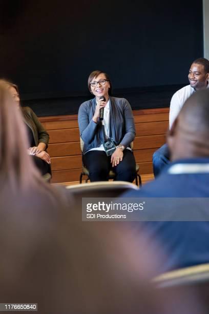 会議中に群衆に話す自信のある中大人のビジネスウーマン - パネル討論 ストックフォトと画像