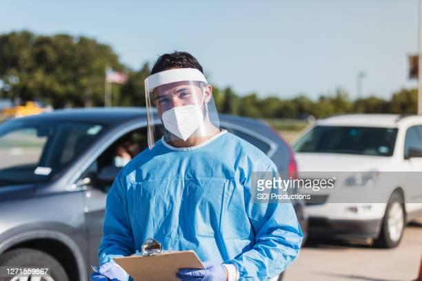 ppeの自信を持って中年の男性医師は、写真のためにポーズ - ドライブスルー検査 ストックフォトと画像