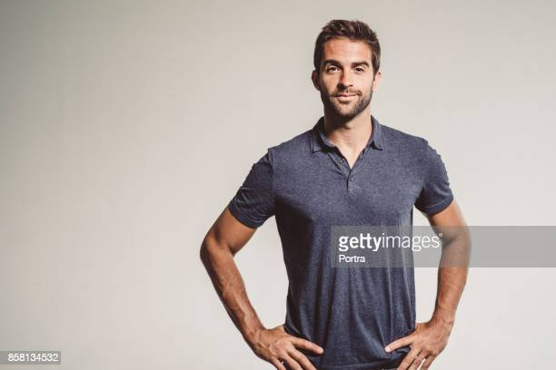 confident mid adult man standing with hands on hip - hand on hip stock pictures, royalty-free photos & images