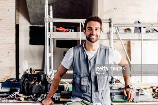confident mid adult mechanic at auto repair shop - waistcoat stock photos and pictures