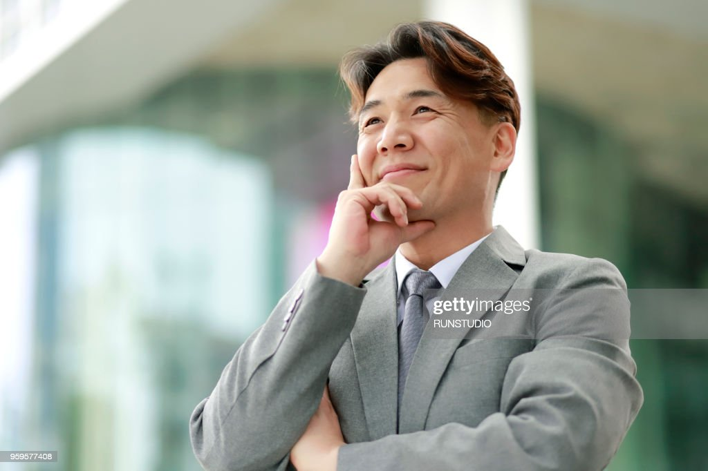 Confident middle aged businessman looking away outdoors : Stock-Foto