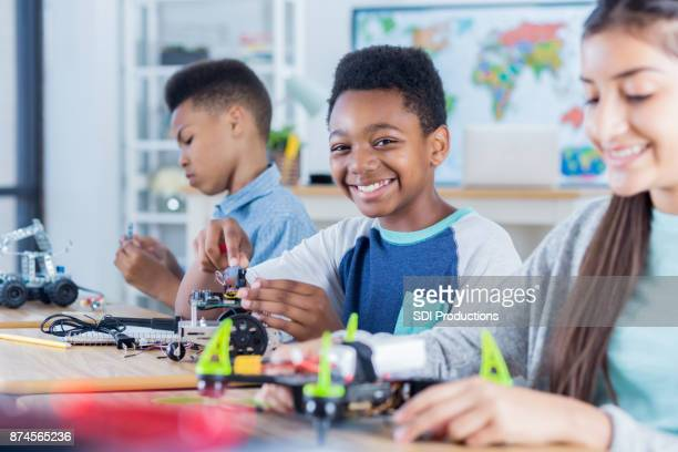 Confident middle school boy works on engineering project
