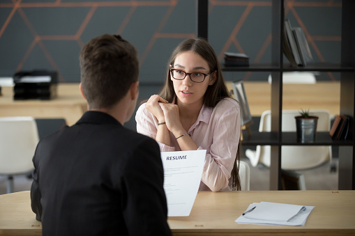Confident millennial female applicant talking at job interview answering questions 963814312