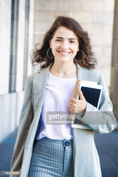 confident millennial female college student walking urban portrait with tablet and books outdoors - one young woman only stock pictures, royalty-free photos & images