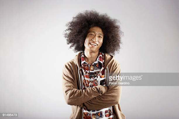 confident mixed race man with arms crossed - big hair stock photos and pictures