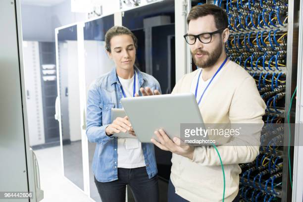 Confident modern engineers discussing bitcoin mining process while synchronizing data from supercomputer and analyzing it on laptop in server room