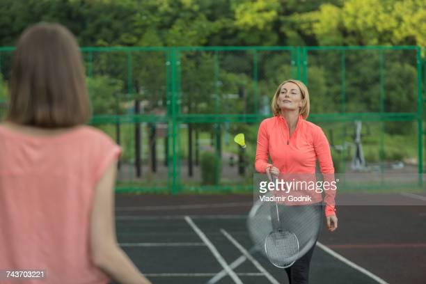 Confident mother playing badminton with daughter in court