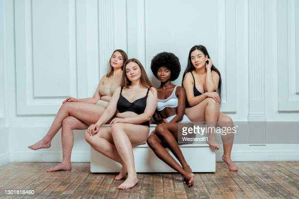 confident multi-ethnic group of models in lingerie  sitting against white wall - bras stock pictures, royalty-free photos & images