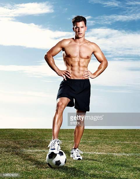 confiante muscular homem de pé no campo de futebol americano - atacante de futebol imagens e fotografias de stock